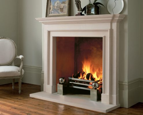Chesneys' Burlington fireplace in Portuguese limestone shown with the Soho fire basket and Spherical fire dogs